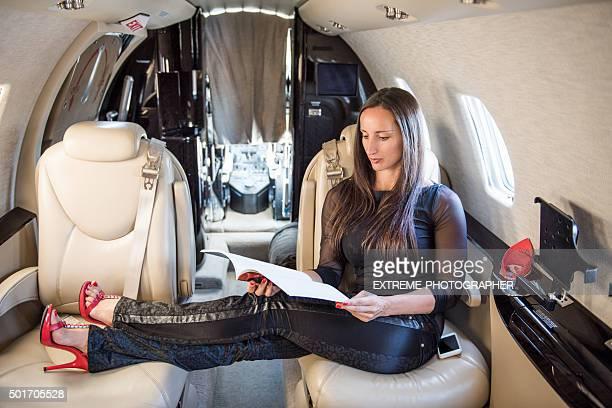 Femme lisant un magazine en avion privé