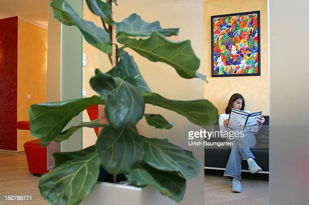 Woman reading a newspaper in the waiting room of a doctors practice