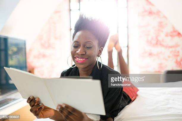 woman reading a novel book on the bedroom