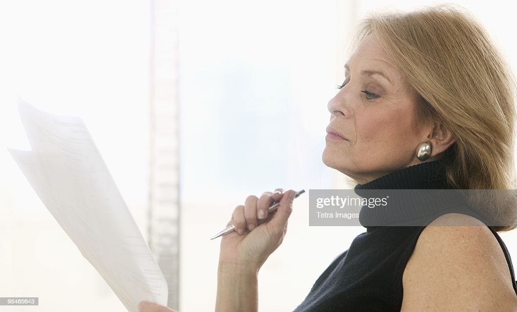 A woman reading a piece of paper and holding a pen : Stock Photo