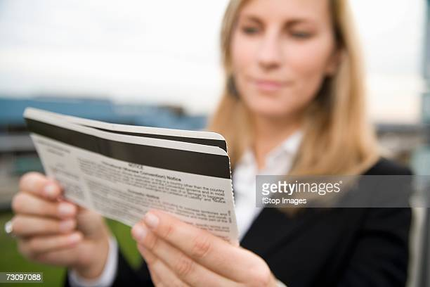 Woman reading airplane ticket outside of airport
