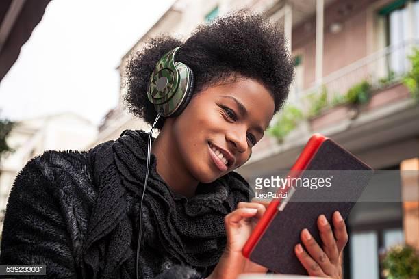Mujer leyendo un libro electrónico sentado en una cafetería
