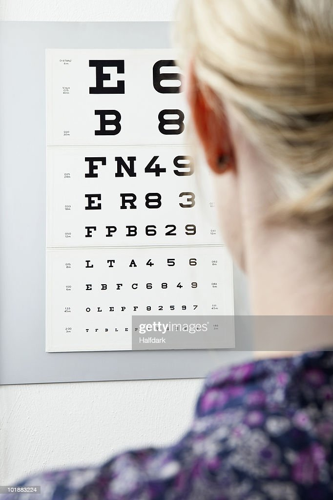 A woman reading an eye chart, over the shoulder view