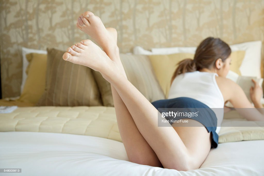 Woman reading and relaxing on bed : Stock Photo