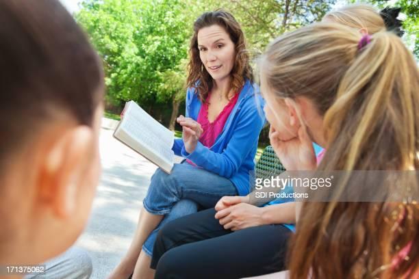 Femme lecture bible avec groupe de jeunes en plein air