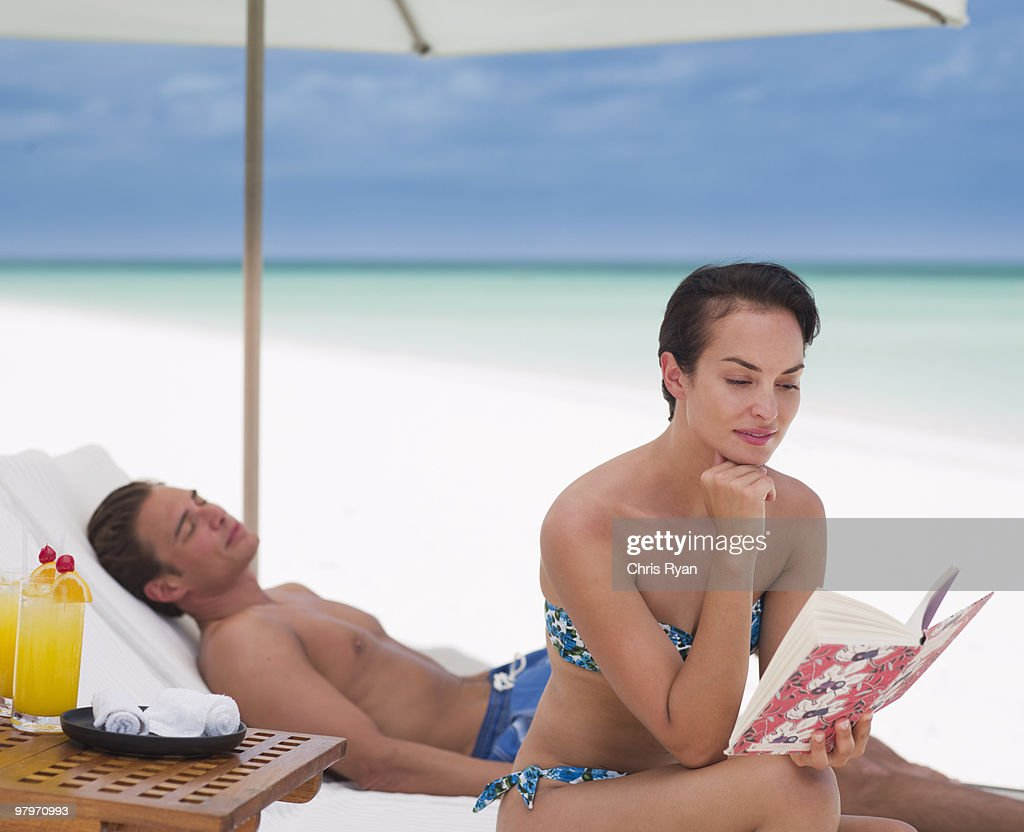 Woman reading book and man laying on lounge chair on beach : Stock Photo