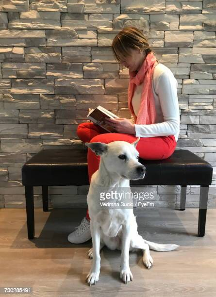 Woman Reading Book By Dog At Home