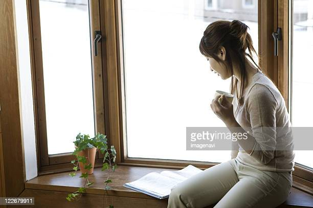 Woman Reading Book by Window