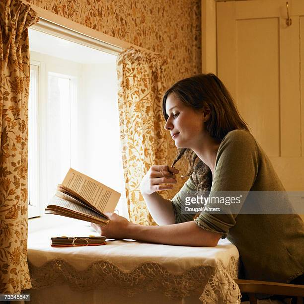 Woman reading book by window, side view