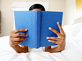 Woman reading book in bed