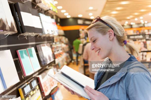 Woman reading book in bookstore
