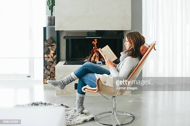 Woman reading book in front of fireplace