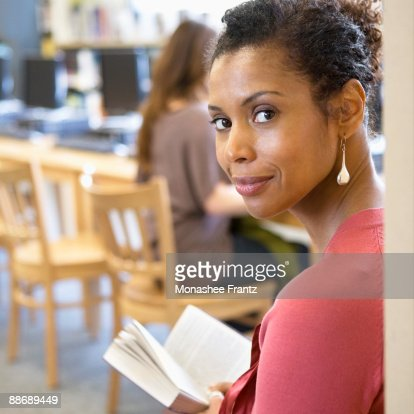 Woman reading book in library : Stock Photo