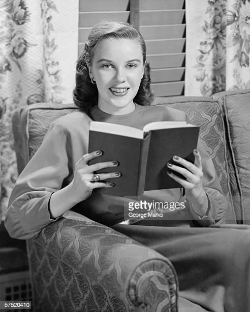 Donna lettura libro in soggiorno, (B & W), verticale