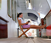 Woman reading book in lounge chair on ship's deck