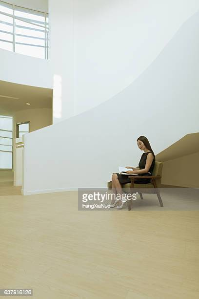 Woman reading book in modern building lobby