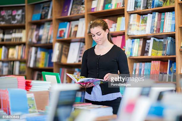 Woman reading book in store
