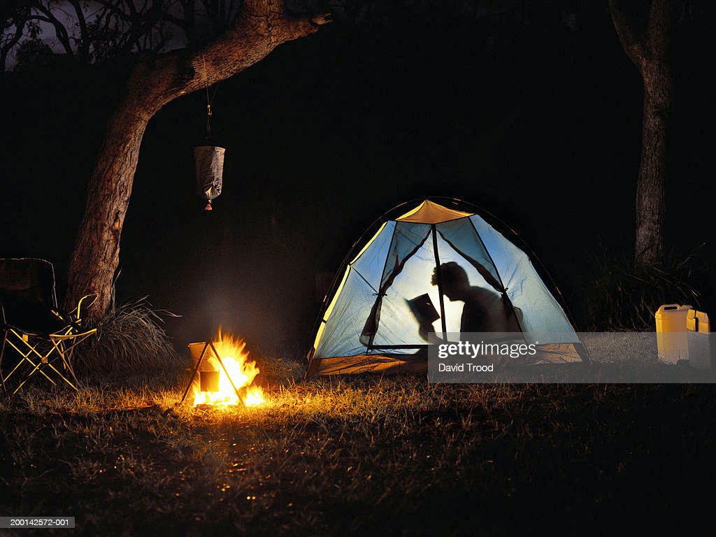 Woman reading book in tent by camp fire, silhouette