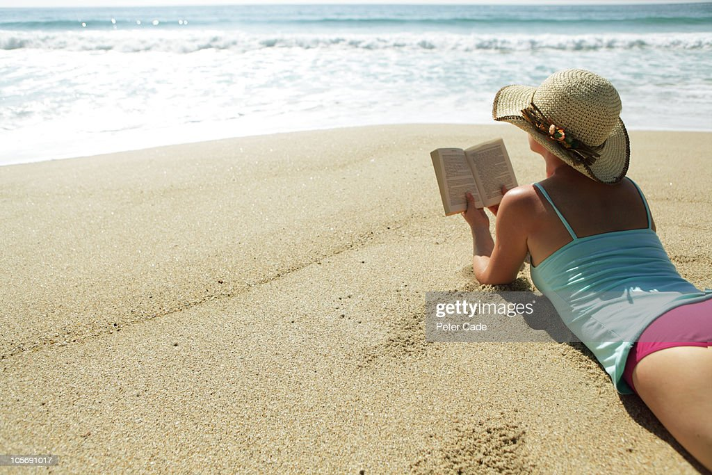 woman reading book on beach : Stock Photo
