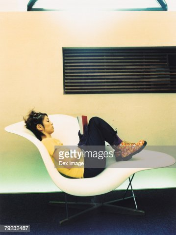 Woman reading book on curved chair : Stock Photo