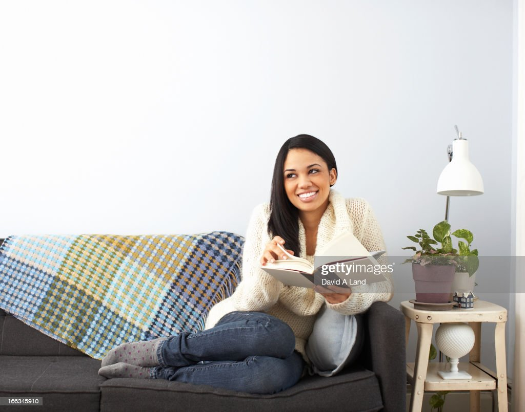 Woman reading book on sofa : Stock Photo