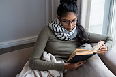 Woman reading book by window on sofa at home