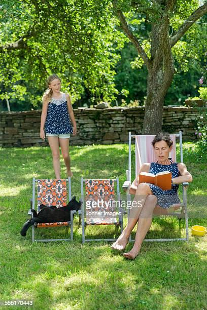 Woman reading book on sun chair