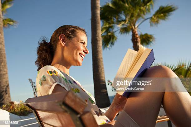 Woman reading book on sunny day
