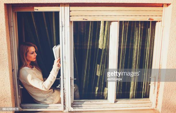 Woman reading book on sunny window at home