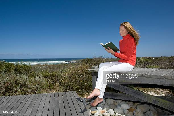 Woman reading book on wooden bench