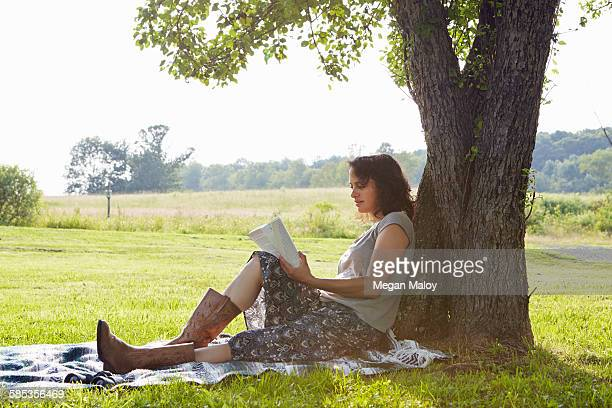 Woman reading book whilst leaning against tree