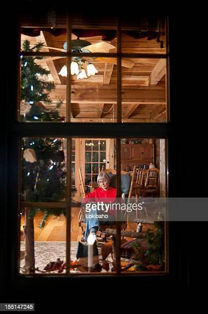 Frau Lesen von rustikalen Weihnachtsbaum, durch Windowpanes