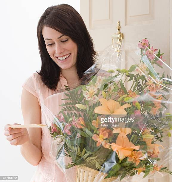 Woman reading card on flower bouquet