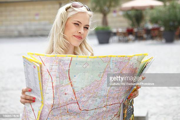 Woman reading city map in courtyard