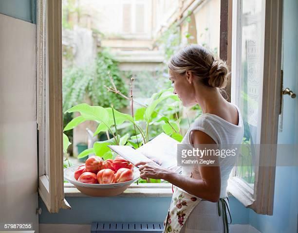 woman reading cookbook at open kitchen window
