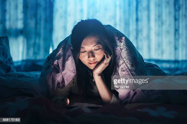 Woman reading digital tablet under the bed sheets