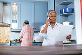 Woman reading document while standing in kitchen at home