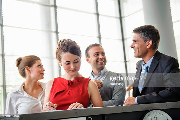Woman reading documents on reception desk surrounded by other business people