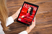 Unrecognisable female reading fashion magazine on tablet computer, view from above