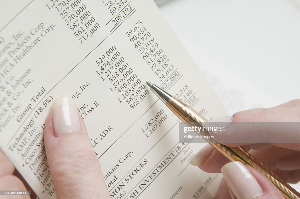 Woman reading financial planning report, close-up : Stock Photo