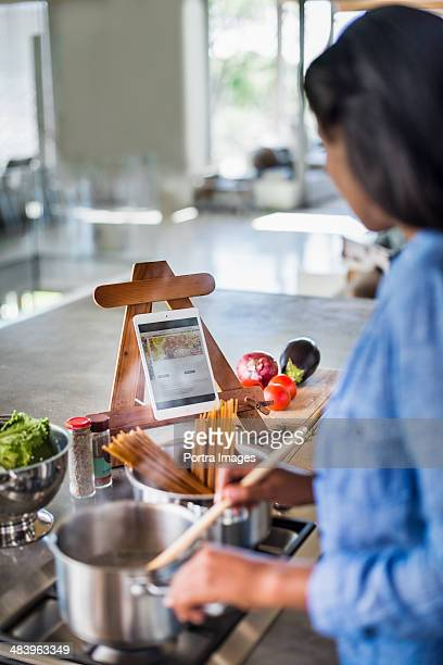Woman reading food blog while cooking