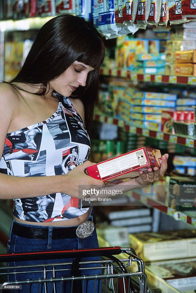 Woman reading food label at a grocery store : Stock Photo