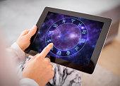 Woman reading horoscopes on tablet