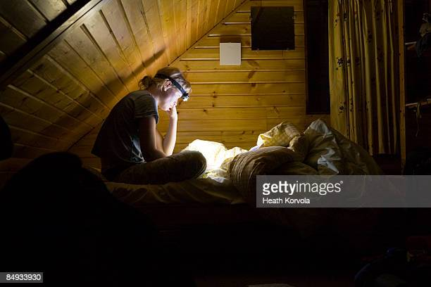 A woman reading in bed by headlamp