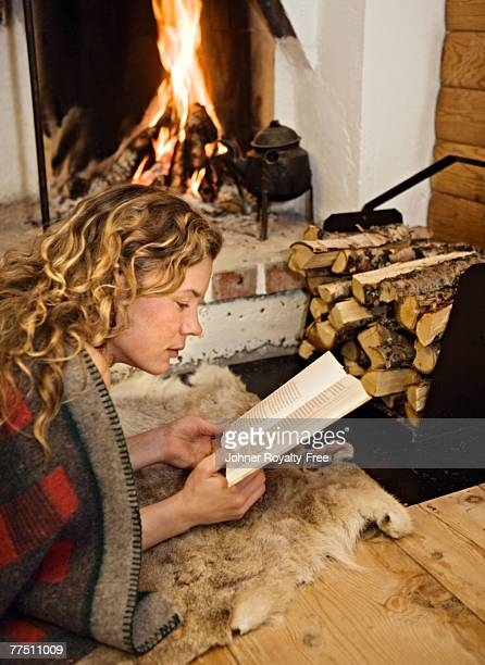 A woman reading in front of  a fireplace Sweden.