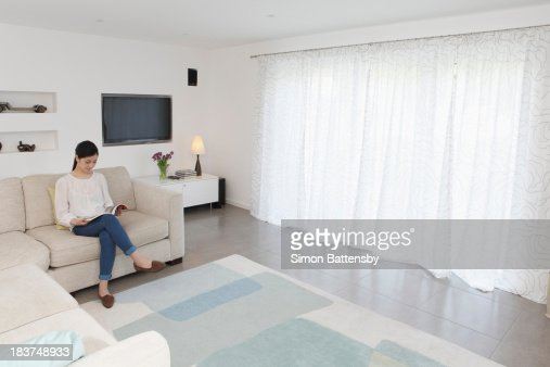 Woman reading in living room : Stock Photo