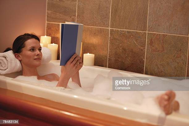 Woman reading in tub