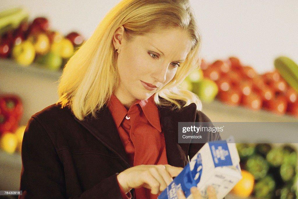 Woman reading label on milk carton : Stock Photo
