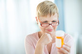 Mature woman with hand on chin reading label on pill bottle