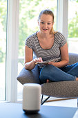 Woman Reading Magazine At Home Asking Digital Assistant Question